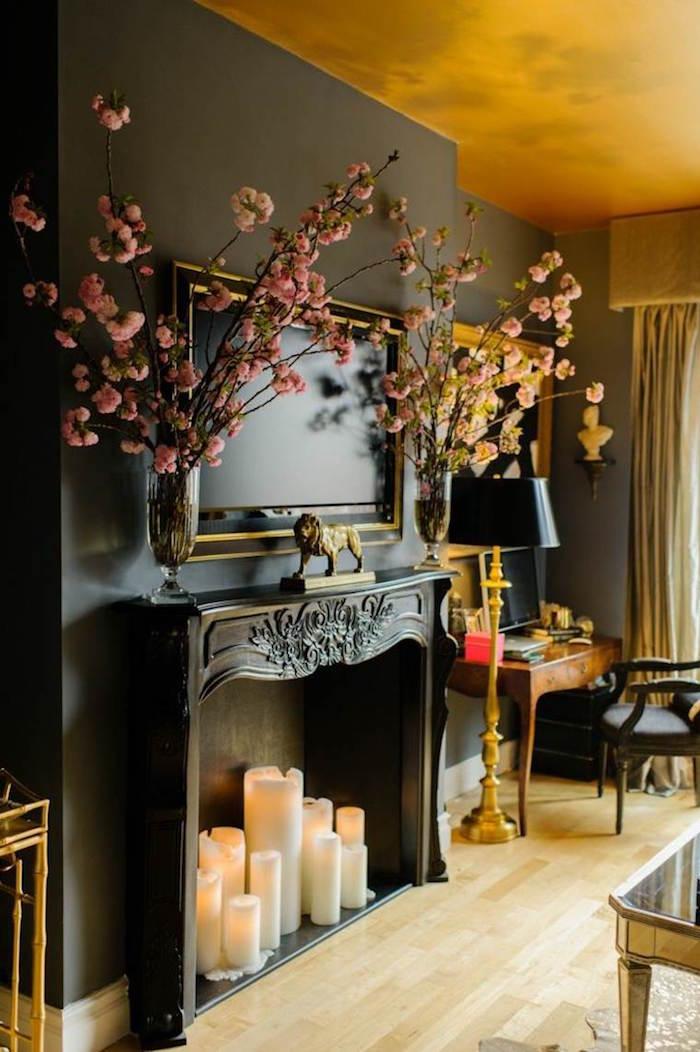 faussé cheminée avec manteau noir avec bougies et tv incrustée dans salon décoration noir et or classy classique design