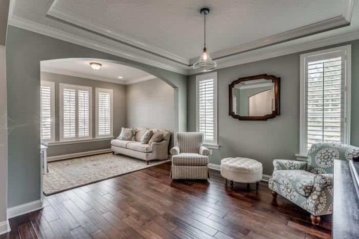 modèle de chambre grise et blanche, aménagement pièce traditionnelle au parquet foncé et plafond blanc avec murs pastel