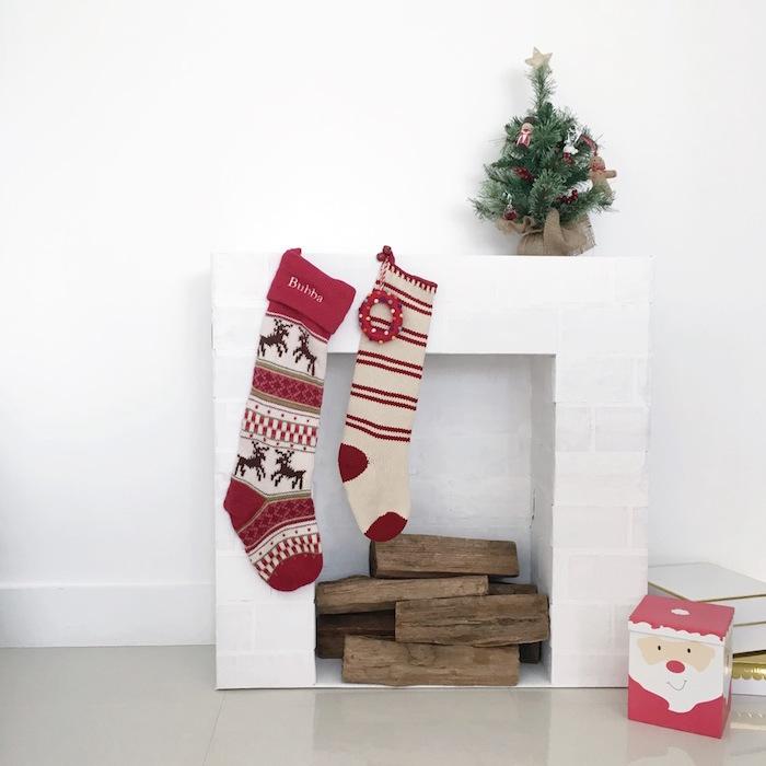 modele petite fausse cheminée de déco imitations briques blanches sur mur blanc avec buches en bois et déco de noel avec chaussettes mini sapin