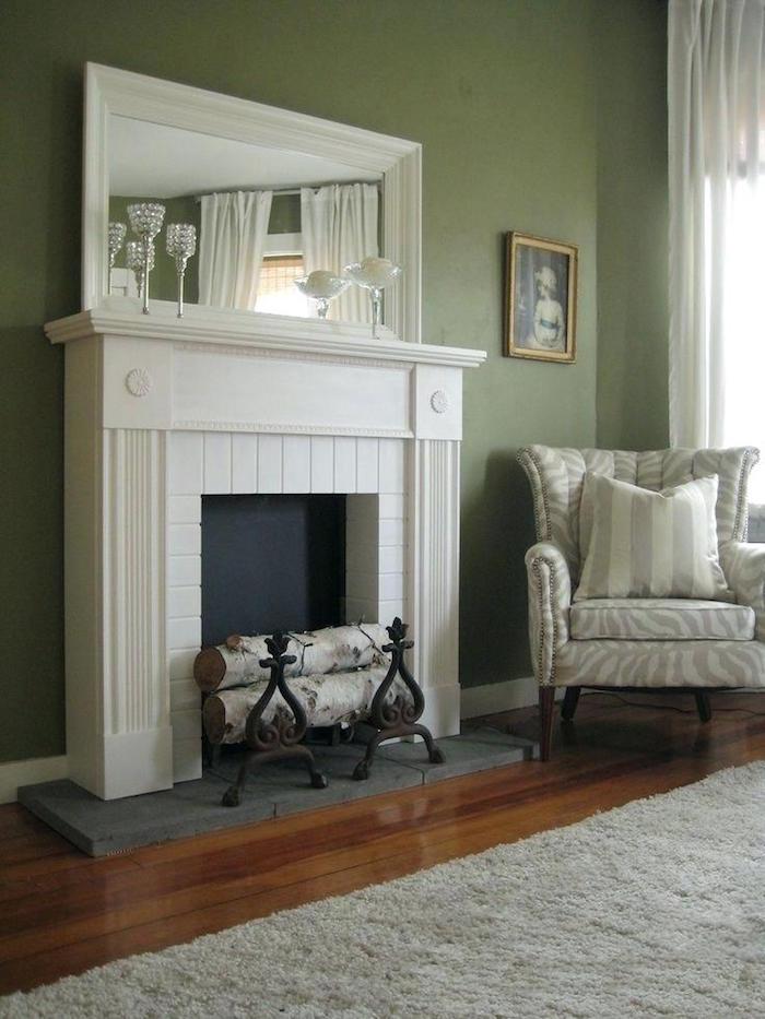manteau de cheminée déco simple avec fond insert noir sur mur vert kaki avec miroir mural et verres en cristal deco et buches en bois moquette grises sur sol parquet foncé