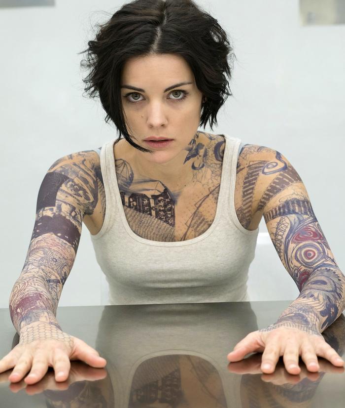 tatouage femme avant bras complet et tattoo abstrait bleu rouge noir poignet épaule poitrine pour fille brune avec debardeur blanc