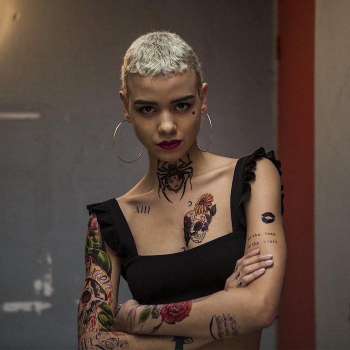 femme aux cheveux courts décolorés blonds avec tatouages sur le bras en couleurs et tattoo araignée sur la gorge et tete de mort calavera sur la poitrine