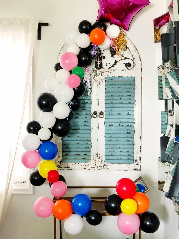guirlande de ballons aux couleurs contrastantes, grand ballon étoile lilas, fenêtre vintage peinte en bleu et blanc