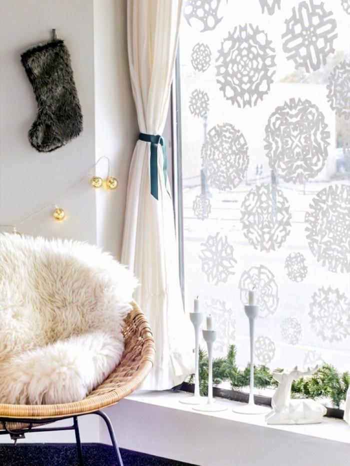 des flocons de neige à motifs variés découpés en papier adhésif et posés sur la vitre d'une fenêtre, coin cocooning avec chaise ronde en rotin et un rebord décoré avec des bougeoirs blancs et guirlande verte, décoration de noel à fabriquer en papier pour orner les fenêtres