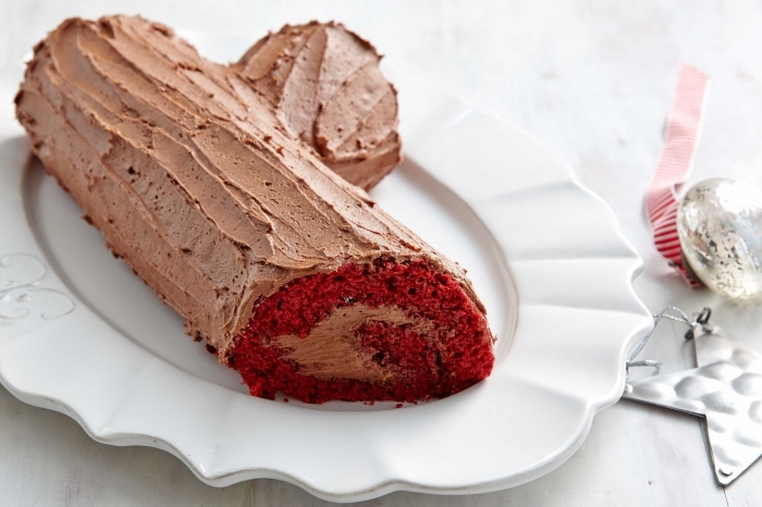 gâteau red velvet cake en forme de bûche de noël originale au glaçage chocolat servie dans une assiette dentelée