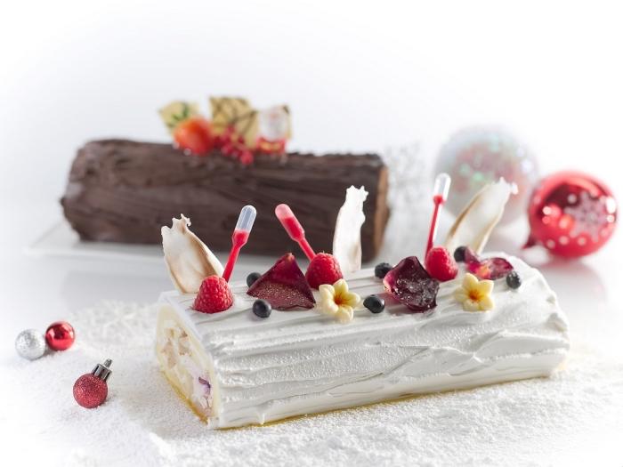 deux versions du gâteau roulé traditionnel, recette de buche de noel au chocolat ou à la vanille décorée avec des fruits rouges et des fleurs comestibles