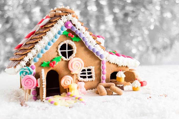 maisonnette pain d épices joliment décorée biscuits au chocolat, bonbons sucrés et petites figurines sucrées