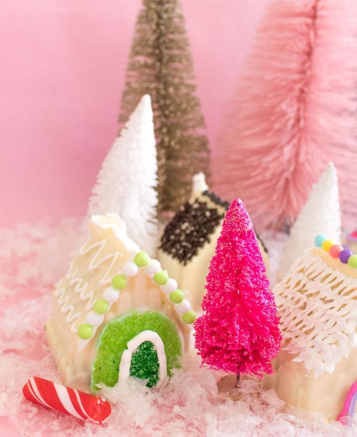 dessert nouvel an et noel, petites maisonnettes pain d épices décorées de chocolat blanc, glaçage royal et gélifiés pour la porte, deco sapins de noel artificiels