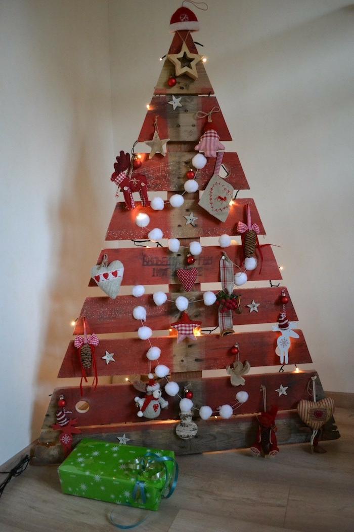 arbre de noel en planches de bois, forme triangulaire créée avec palettes, guirlande de pompons, cerfs, coeurs et étoiles, petites figures en textile