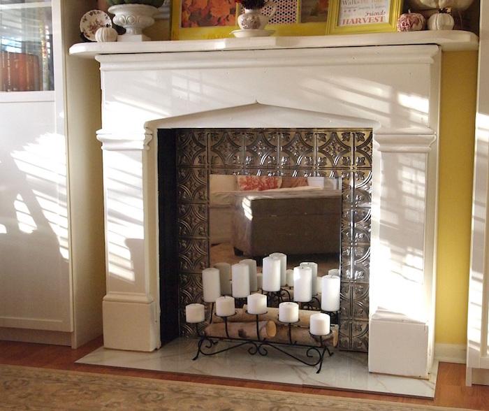 cheminée déco avec manteau blanc et fond insert en métal forgé et chandelier bougies blanches et mini buches décoratives