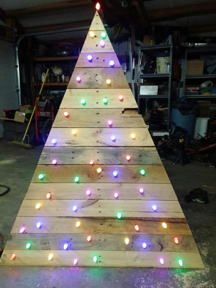 grand sapin fait avec palettes, sapin artificiel décoré de petites lumières colorées, arbre de noel en bois