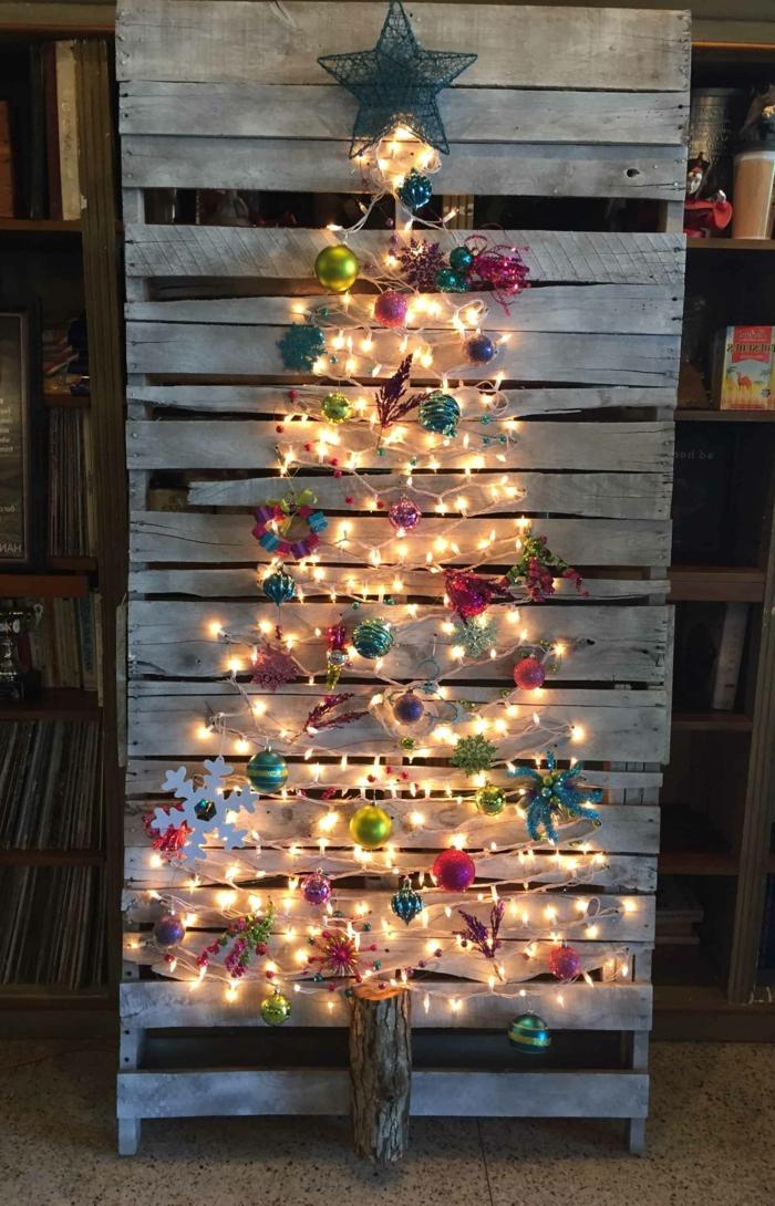 jolie déco de noel avec palette, multitude de jouets multicolores, flocon de neige en papier, guirlande lumineuse, étoile de fil bleu, petit tronc