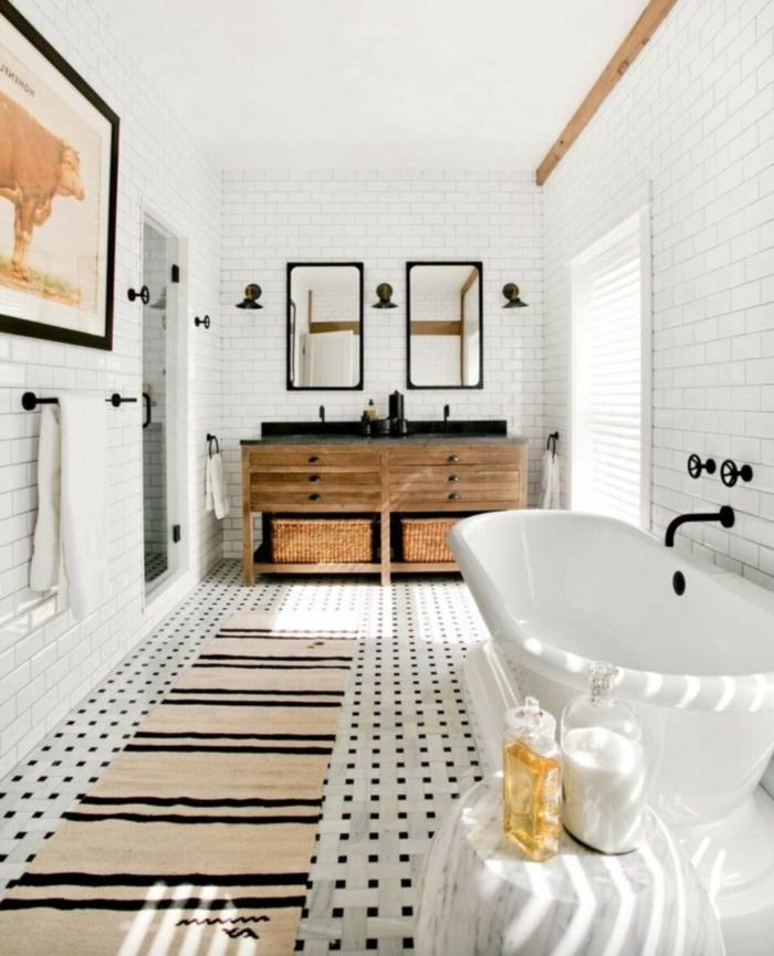 jolie salle d'eau, tapis beige aux rayures noires, meuble sous vasque bois usé, carreaux muraux blancs, grande photographie encadrée