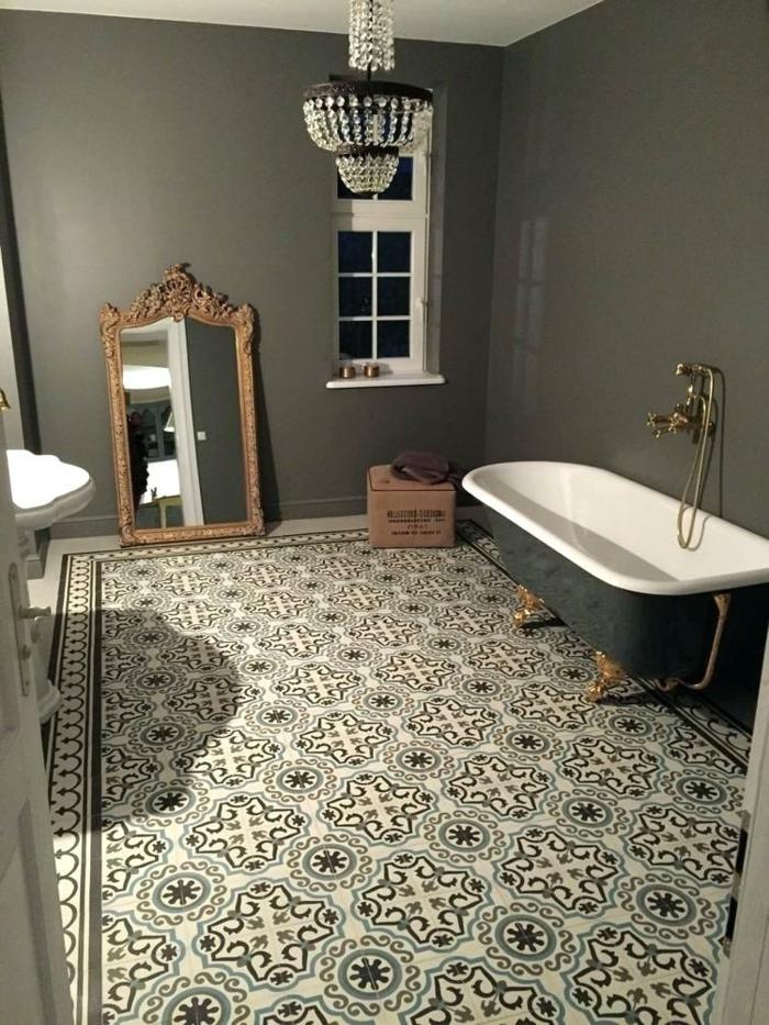 carreaux de ciment au sol d'une salle de bain en gris et blanc, miroir au cadre baroque, baignoire en fonte et robinet mural, plafonnier oriental