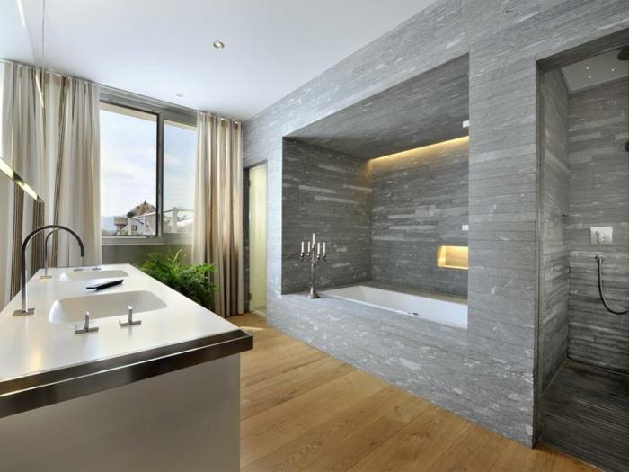 salle de bains spacieuse avec grande fenêtre aux rideaux beiges, baignoire à encastrer dans une niche grise et douche ouverte