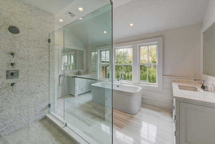 salle de bain blanche, grande salle avec baignoire céramique, douche minimaliste, spots au plafond, meuble vasque blanc