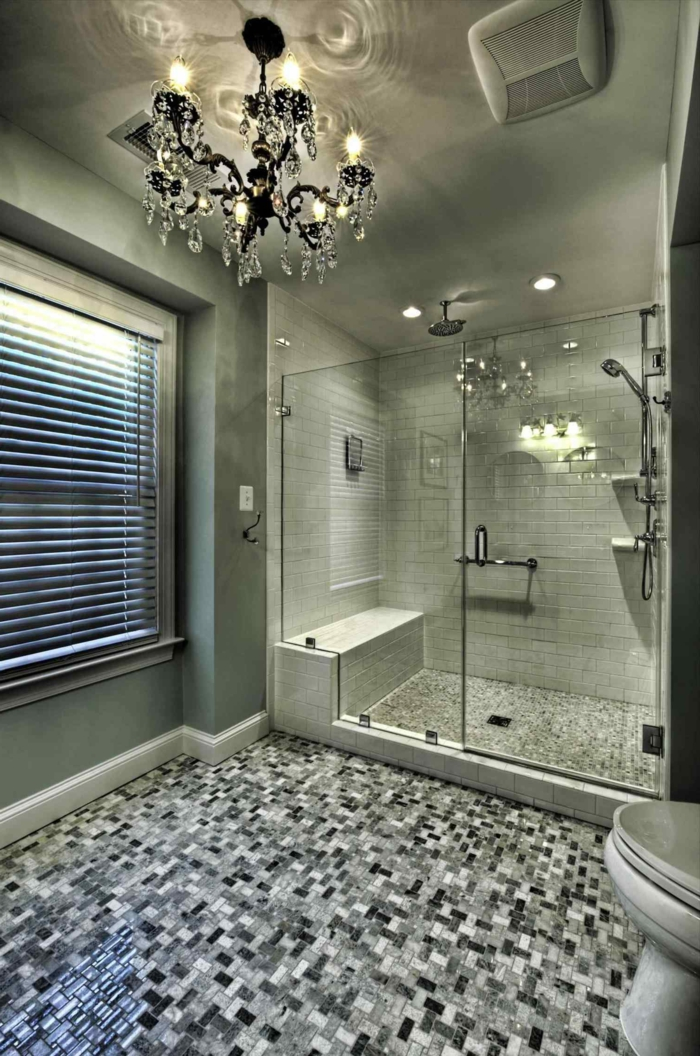 salle de bain en gris, petites tuiles mosaiques au sol, grand plafonnier baroque pampilles, banquette de douche
