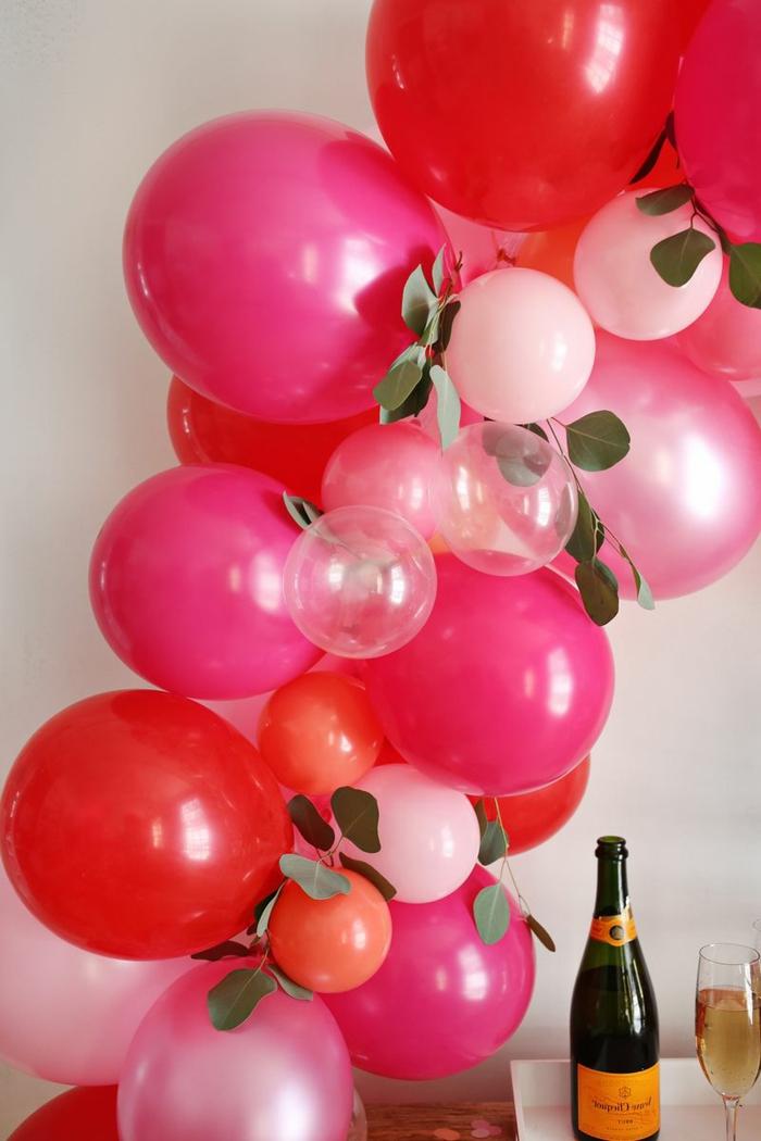 grands ballons cyclamen et petits ballons roses et transparents, feuilles décoratifs, bouteille de champagne et verre