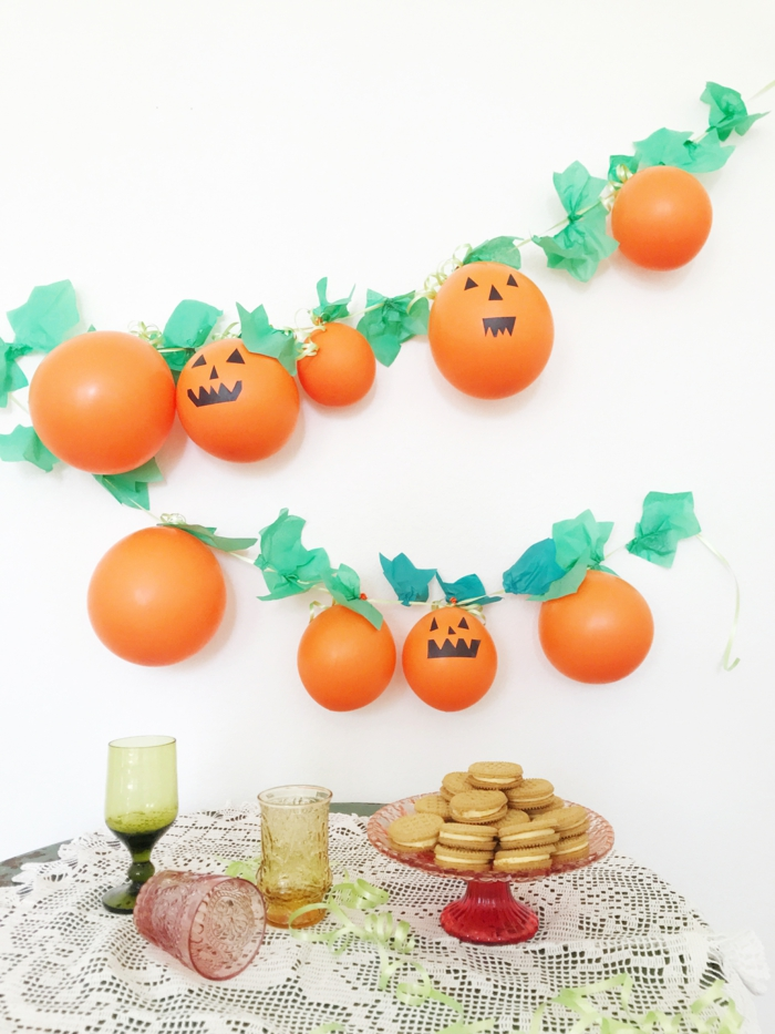 guirlande de ballons originale, ballons citrouille attachés à une ficelle, feuilles vertes en papier, biscuits à la crème