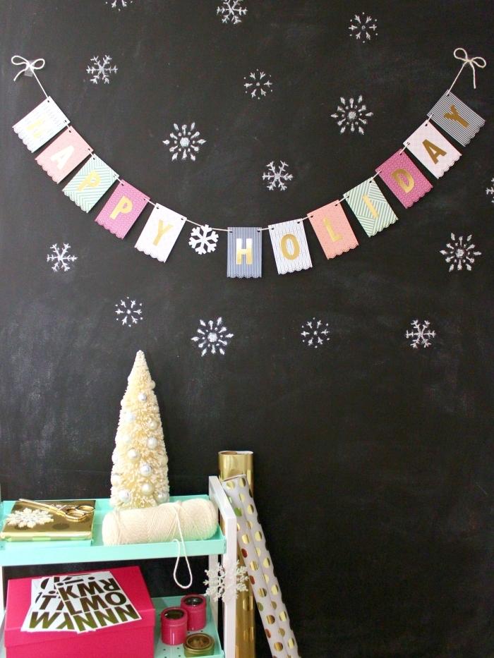 guirlande de noël joyeux noël de petits fanions en papier imprimé à bordure dentelée, posée sur un mur en ardoise
