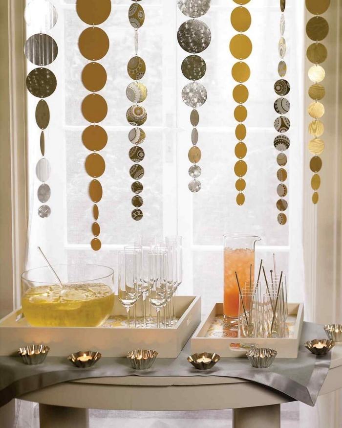 des guirlandes de noël en papier composés de confettis ronds aux tons de l'or et de l'argent derrière le buffet festif, décoration de noel à fabriquer en papier