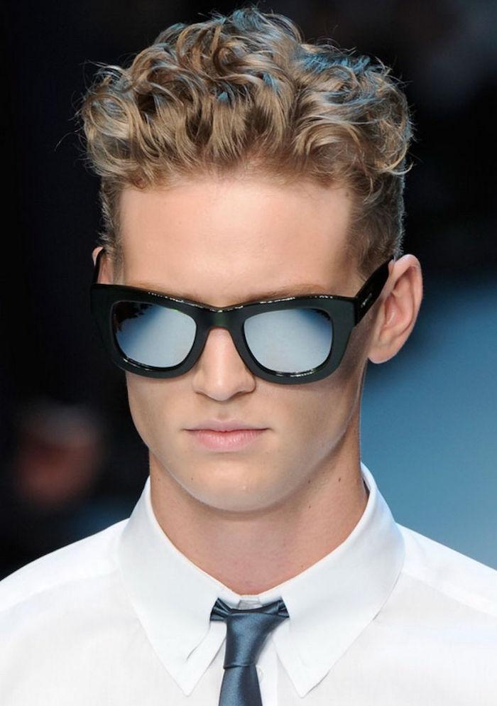 homme blond aux cheveux bouclés avec dégradé et dessus plus long et lunettes de soleil et chemise blanche