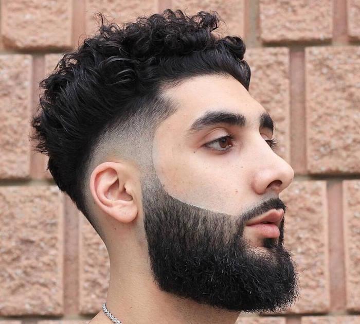 homme brun oriental avec coupe tendance dégradé tres court bas autour des oreilles et cheveux bouclés et longue barbe noire taillée