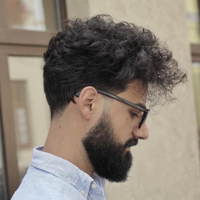 homme brun avec cheveux frisés mi long vers l'avant style banane et barbe noire taillée en dégradé