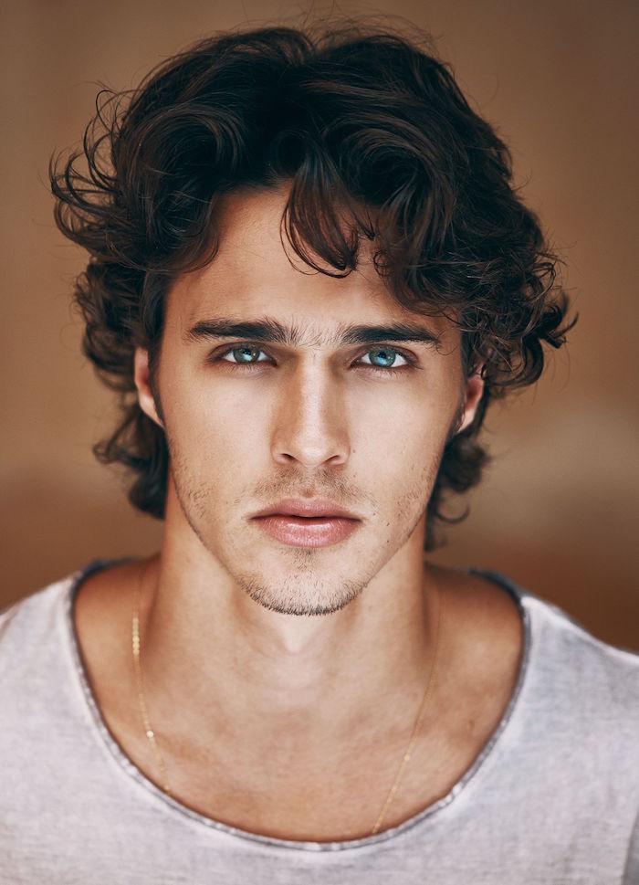 coiffure homme brun aux cheveux ondulés tombant mi longs et yeux bleus avec tee shirt gris chiné