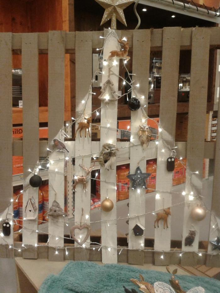 sapin en blanc peint sur une palette, déco arbre de noel lumières en guirlande blanche, cerfs, sapins et étoiles, hiboux et boules dorées et argentées