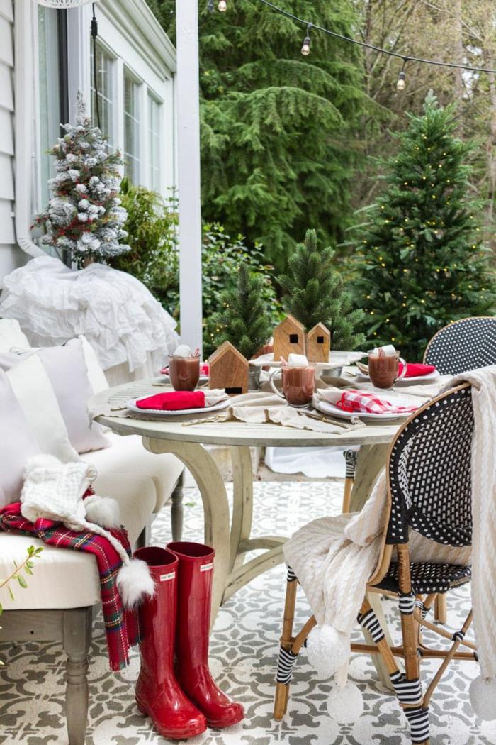 id e deco de table noel table  caf  ext rieure bottes rouges maisonettes en bois serviettes rouges assiettes blanches couverture de table carr s boissons chaudes
