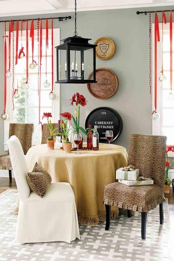 guirlandes de noël suspendues aux tringles à rideaux, composées de boules de noël argent attachées avec ruban rouge