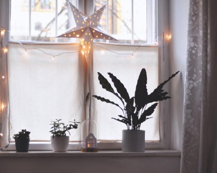 déco fenêtre de noël avec une grande étoile en papier 3d, guirlande lumineuse et une maison en papier sous cloche en verre posée sur le rebord