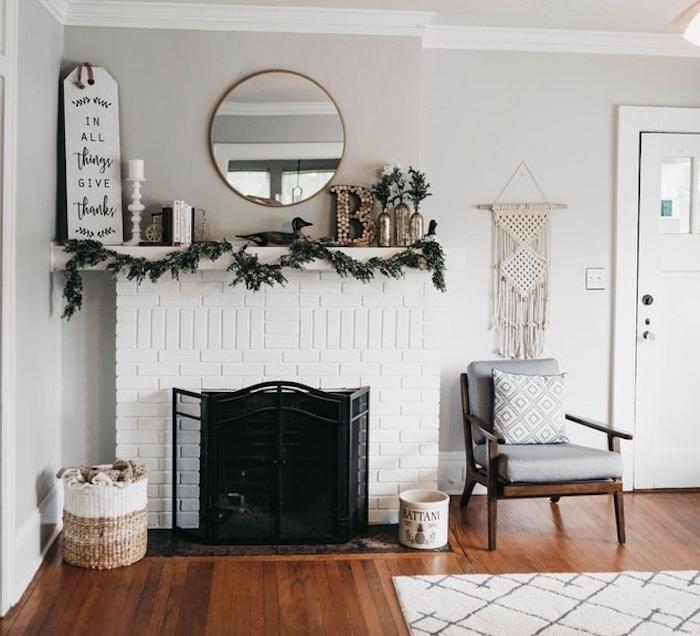 exemple de cheminée moderne style traditionnel à foyer ouvert, manteau de cheminée blanc, grille noire, deco salon gris, miroir rond et parquet marron, exemple salon rustique