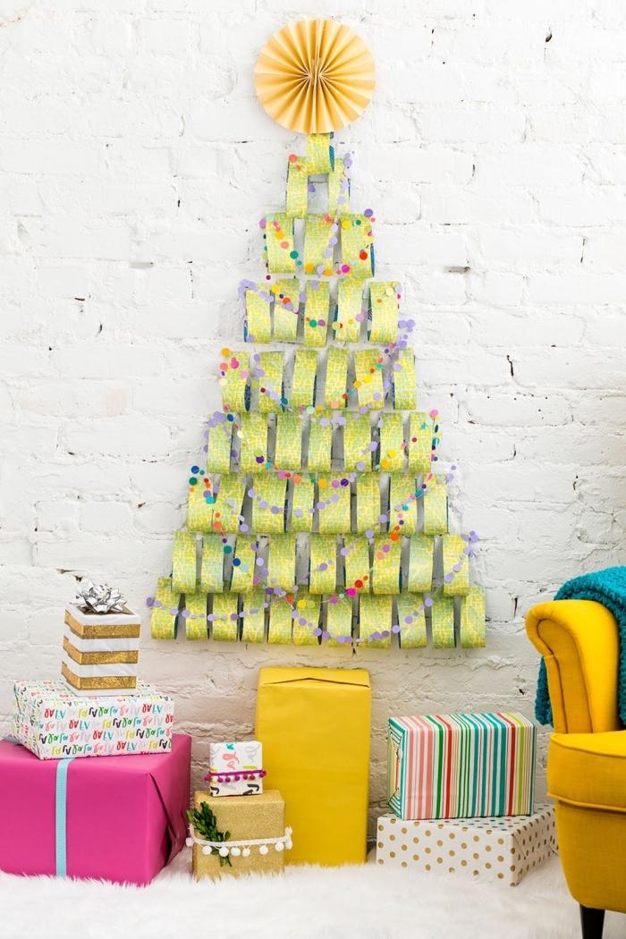 decoration de noel fait main pour les murs, bandes d'emballage cadeaux collées au mur en forme de sapin original qui se termine par une rosace en papier jaune