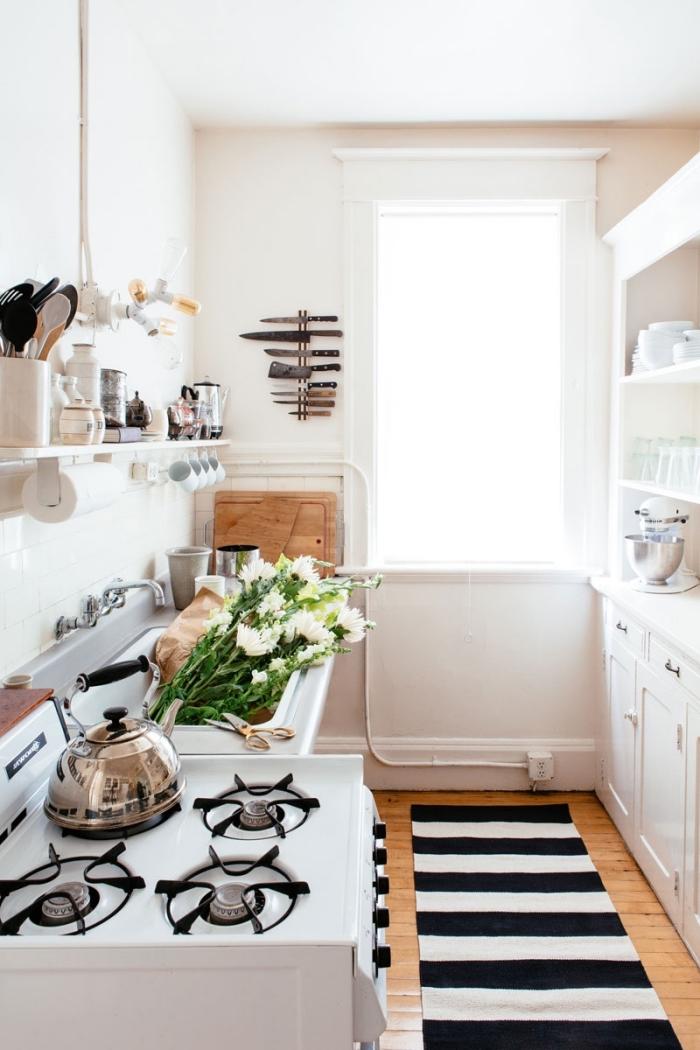 l'amenagement petite cuisine en longueur avec un buffet de cuisine vintage le long de l'un mur et une étagère ouverte à crochets sur l'autre mur, un support aimanté pour couteaux