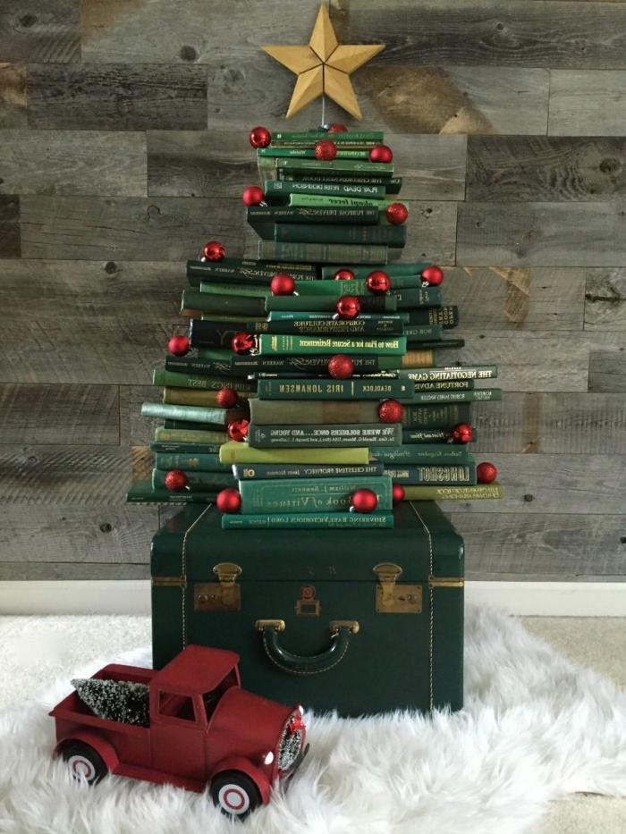 un tas de livres anciens aux couvertures vertes qui forment un joli sapin de noel original, posé sur une valise ancienne et un tapis douillet blanc