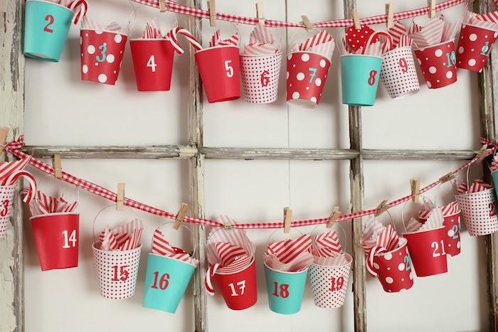 petits seaux décoratifs cartonnés suspendus sur un ruban rouge et blanc à des pinces à linge de bois sur cadre volet bois brut, idee de calendrier avent