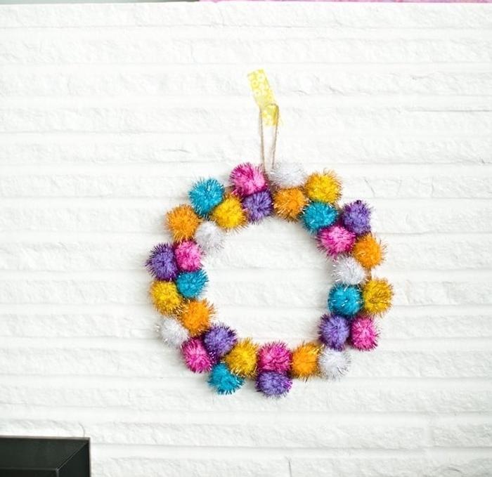 couronne de noel originale fait main en pompons colorés pailletés, accrochée sur un mur blanc, deco noel maison simple