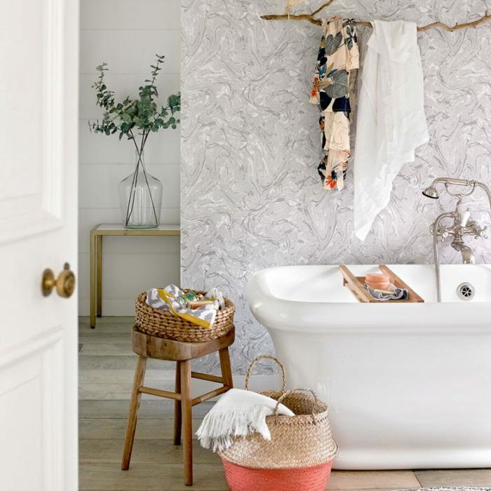 panier rose rustique, baignoire, papier peint rendu marbré, table console et grand vase en verre, robinet ancien