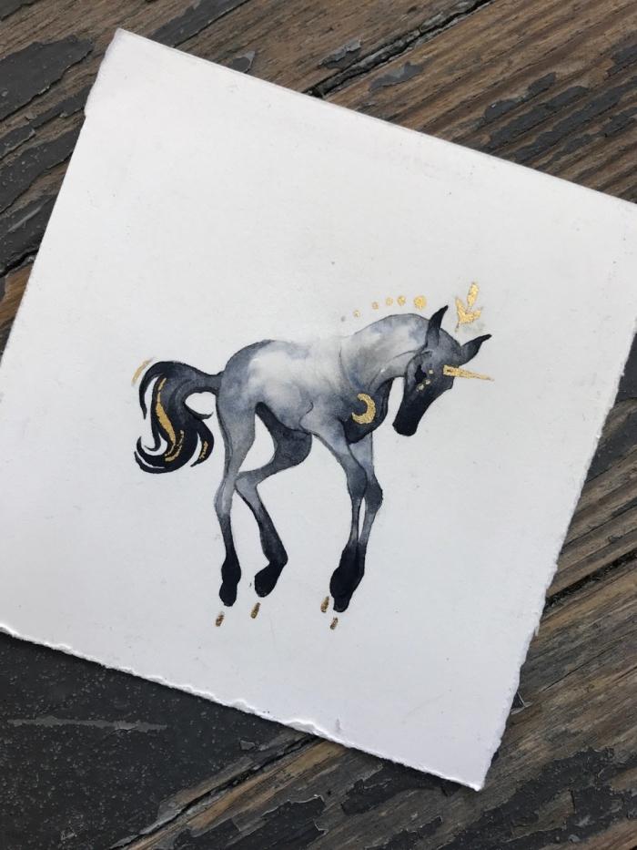 dessin de licorne facile et originale coloré à l'aquarelle en nuances de gris, parsemée d'or, dessin de créature de fantaisie qui semble flotter dans l'air