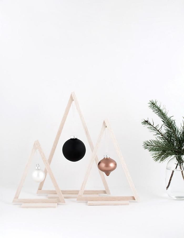 des triangles en bois transformés en sapins décoratifs graphiques et minimaliste avec une suspension de boule de noel