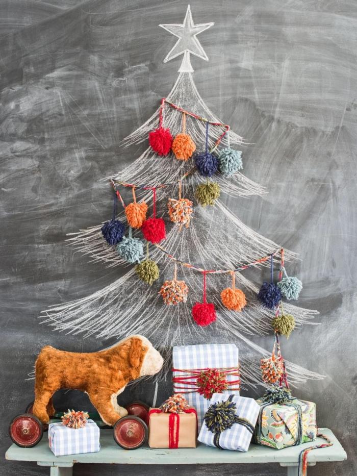 quelle alternative écolo et originale à l'arbre de noël classique, un sapin dessiné à la craie sur un mur en ardoise, décoré d'une jolie guirlande de pompons en laine multicolores