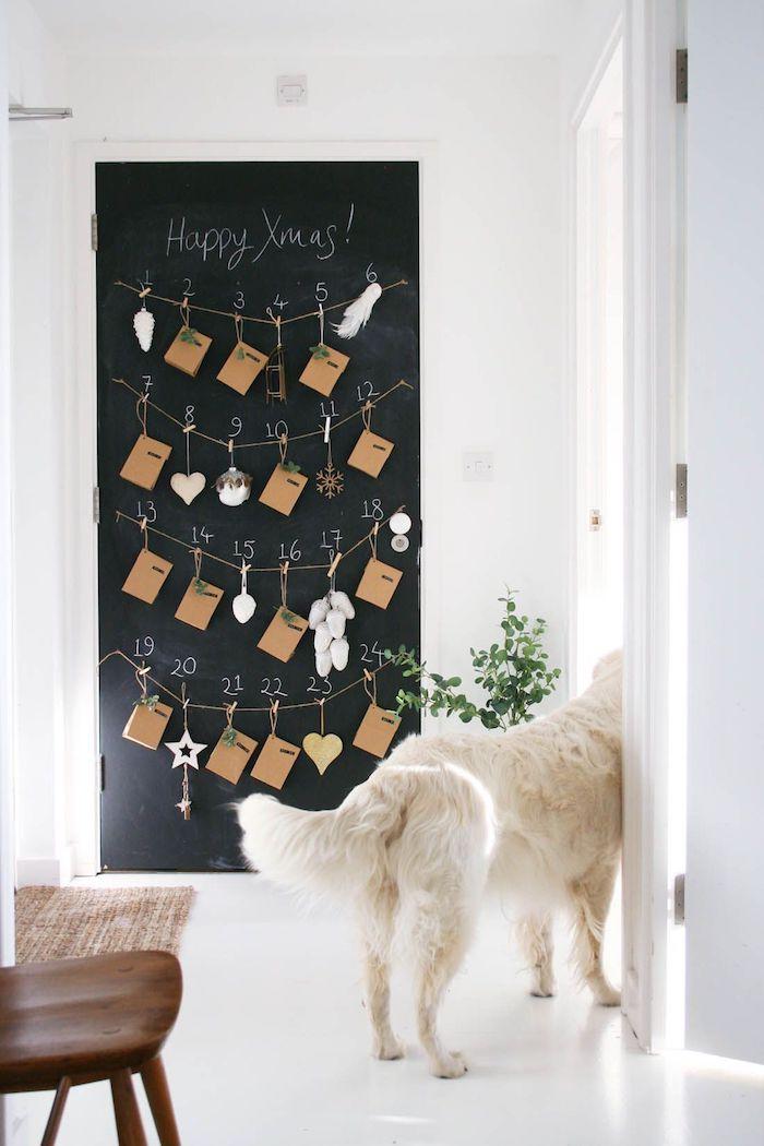 calendrier de l avent en tableau noir peinture à la craie avec des cartes papier kraft suspendues et petites décorations de noel