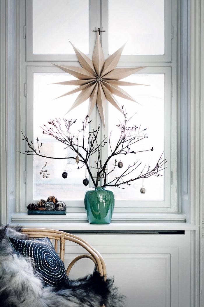 grande étoile 3f en papier à suspendre à la fenêtre, décoration de noel a fabriquer pour adultes, décoration de rebord de fenêtre avec des branches en vase et un plateau de boules de noël