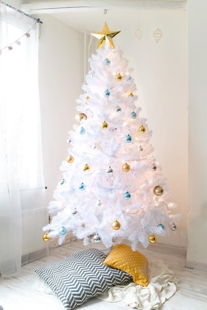 sapin de noel blanc décoré de petites boules de noël en or, bleu et argent avec un couvre-pied de coussins imprimé géométrique