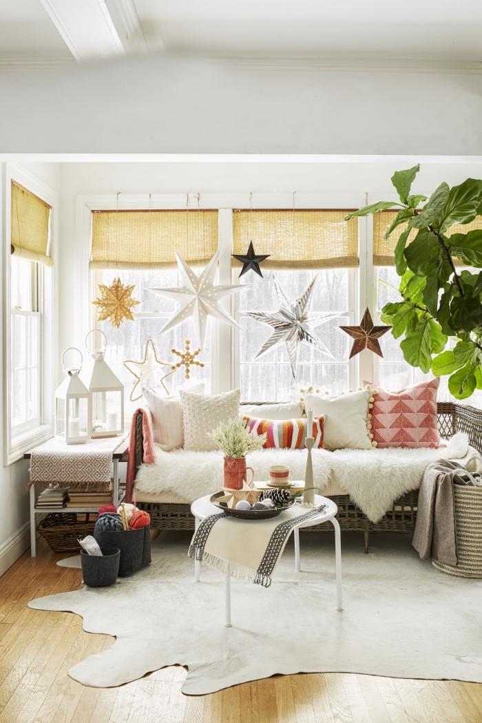 déco fenêtre de noël originale avec de grandes étoiles en papier métallisé suspendues sur la barre à rideaux, déco salon cocooning avec canapé couvert de plaid douillet et d'une multitude de coussins