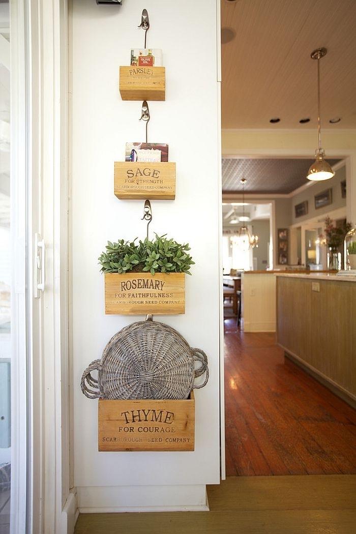 de petites caisses vintage suspendues à des crochets sur un pan de mur dans la cuisine, transformée en étagères et jardinières murales