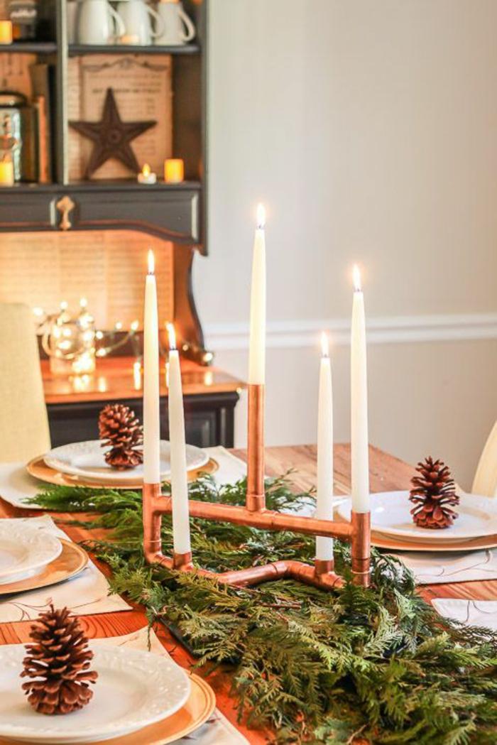 joli centre de table en cuivre porte bougies chemin de table en branches de pins assiettes blanches pommes de pin bougies allum es