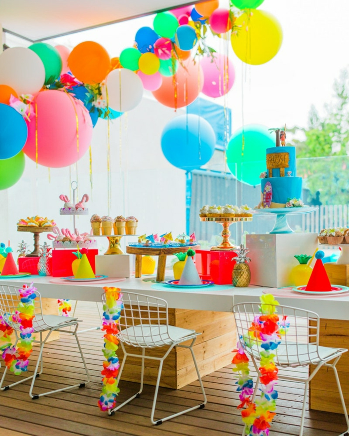 chaises blanches, table blanche, ballons suspendus, présentoir à gâteau avec gâteau bleu et plateaux dorés avec cupcakes